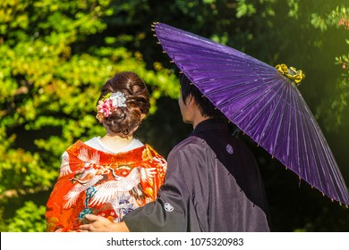 Couple in love with typical Japanese clothing and colorful umbrella in a garden of Tokyo, Japan
