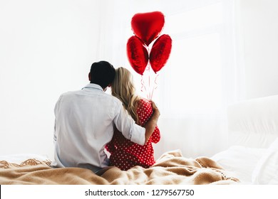 Couple. Love. Valentine's day. Back view of man and woman sitting on the bed, she is holding red heart-shaped balloons