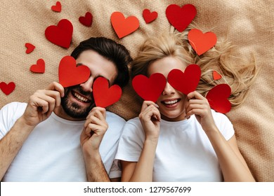 Couple. Love. Valentine's day. Man and woman are holding red paper hearts and smiling; top view
