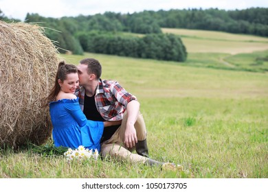 couple in love in a village field at sunset