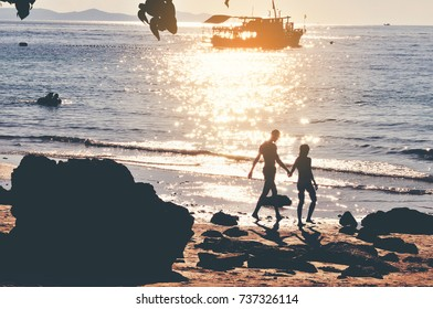 A couple of love walking on the beach and have a boat in the sea behind background with flare light,silhouette,reflections,Thailand.