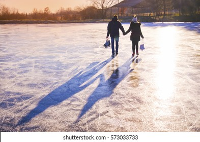 Couple in love walking on the ice with skates in hands during calm winter sunset - active wallpaper for valentine
