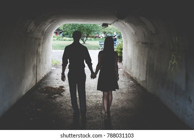 A couple in love walking through a tunnel holding hands in the Spring.
