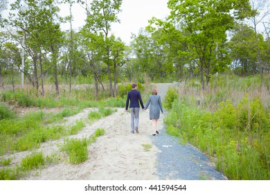 Couple in love walking in the woods. Man and woman holding hands walking along the road. Forest. Love. A family.