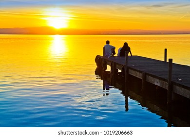 couple in love watching the sunset from the jetty