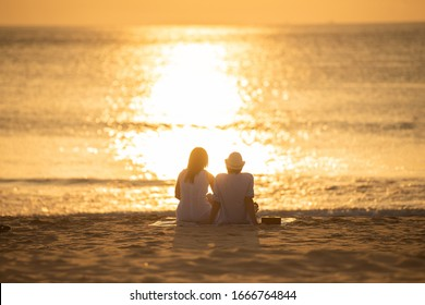 Couple in love watching sunset together on beach travel summer holidays. People silhouette from behind sitting enjoying view sunset sea on tropical destination vacation. Romantic couple on the beach.