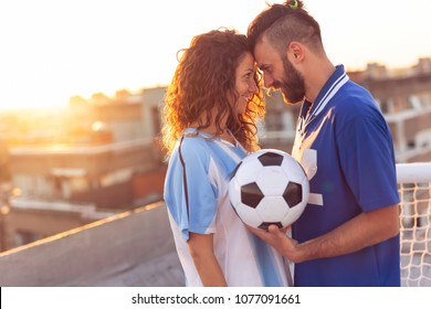 Couple in love wearing football jerseys, standing on a building rooftop after a match and enjoying a beautiful sunset over the city