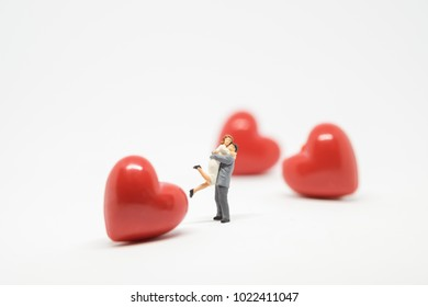 Couple in love, wedding and Valentine's Day concept. Miniature figures of man and woman in love standing with mini red heart in white background and copy space for text