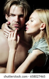 couple in love of woman with cute face, makeup and long, blond hair touching unshaven cheek of handsome man with beard and naked shoulders on black background. Skincare, beauty