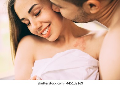 couple in love wrapped in a towel, hugging on the balcony
