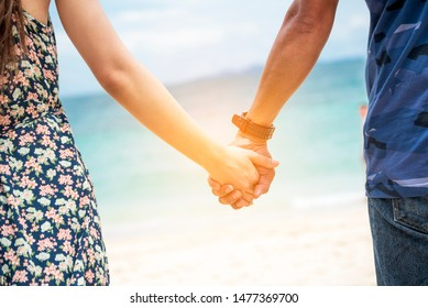 Couple lover hold hands together on tropical summer beach. Focus on hands with happiness activity. Romantic love travel togetherness. Summer vacation lover lifestyle concept.