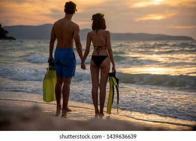 Couple lover holding hands together on the beach during sunset on honeymoon trip at tropical summer island. Honeymoon adventure trip for young couple traveler.