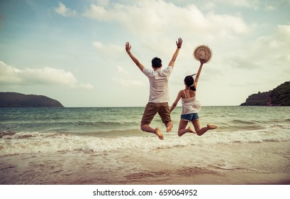 couple lover jump on the sand beach together, happy honeymoon trip.