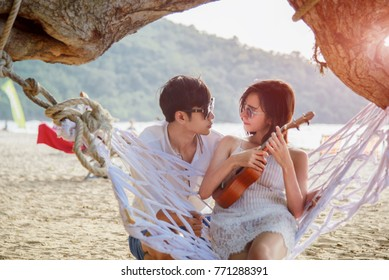 couple lover in romantic on the hammock hang on the tree at the sea beach, enjoy and happy on honeymoon vacation