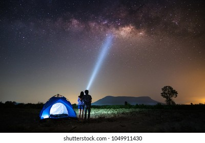 Couple Lover standing near the tent and looking milky way and stars on the sky at night.silhouette style.this picture may have some noise.