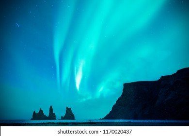 A couple or lover is watching blue and green aurora borealis or northern light at Black sand beach and Reynisdrangar basalt rock during night sky in winter in Iceland,Europe.it is beautiful landscape.