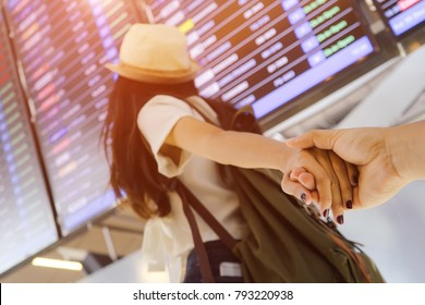 Couple lover woman holding hands boyfriend walking to information board at airport with backpack for buying ticket travel in summer vacation on terminal man follow girlfriend tourist honeymoon