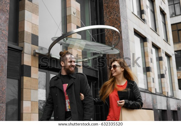 Couple lovers after shopping day walking in street of modern city and laugh. Modern and stylish family goes home and talk about evening plans. Hipsters planning party with friends in the weekend.