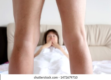 Couple of lovers in a bed, surprised woman looking on a naked man standing in front of her with spread legs. Concept of penis size and erection, foreplay before sex