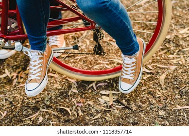 Couple of lovers with green sneakers and jeans standing next to a vintage bicycle
