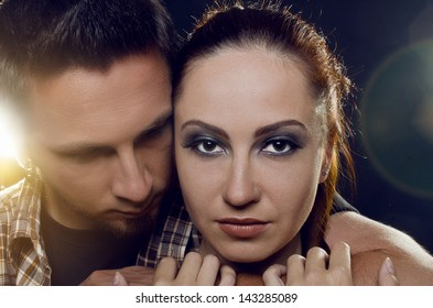 Couple of lovers. The guy holding the girl's neck, hugging her tightly, looking at her. The girl with two hands holding a hand guy and looking at the camera. On a black background