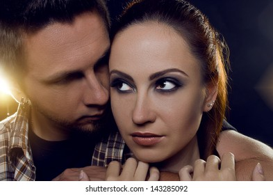 Couple of lovers. The guy holding the girl's neck, hugging her tightly, looking at her. The girl with two hands holding a hand guy and looks away. On a black background