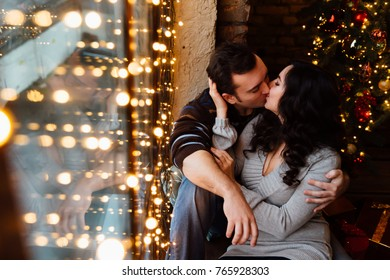 Couple of lovers hugs sitting on the windowsill in the Christmas loft studio. guy is hugging the girl. Garlands and New Year's lights. backdrop of a Christmas tree. Bokeh. kiss.
