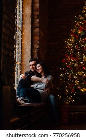 Couple of lovers hugs sitting on the windowsill in the Christmas loft studio. guy is hugging the girl. Garlands and New Year's lights. backdrop of a Christmas tree. Brick wall. Gifts box.