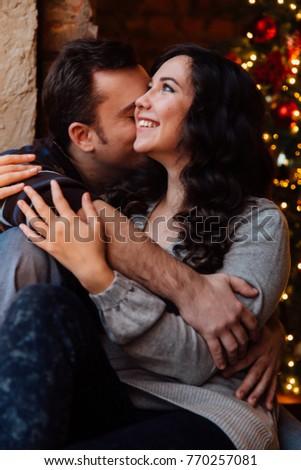 The Christmas Loft.Couple Lovers Hugs Sitting On Windowsill Stock Photo Edit