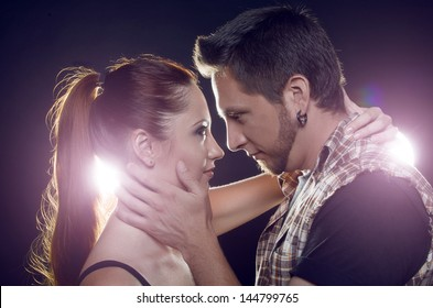 Couple of lovers. Couple of independent steep young people hugging, looking into each other's eyes, on a black background with two luminous lanterns