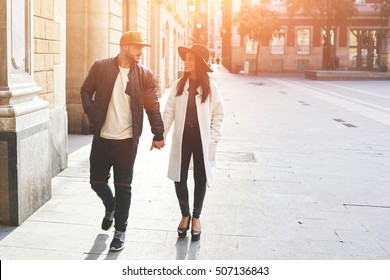 Couple of lovers leisurely stroll in the cool autumn morning on the streets of a Spanish town.The guy holds his wife's hand and tenderly looking at her.Pretty woman in black hat and white coat smiling