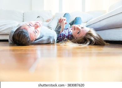 Couple of lovers in the living room holding hands and lying on sofa,concepts about domestic life, relationship and living together