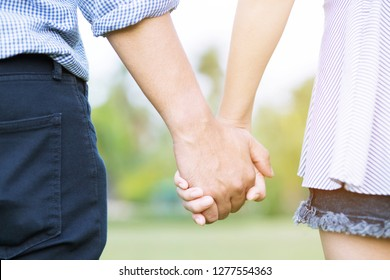 Couple lovers romantic holding hands towards with bright sun flare in public parks, or close up view in a conceptual image first love adolescent young relationship. lover
