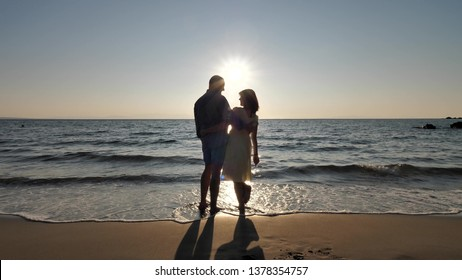 Couple of lovers silhouettes holding hands go to the sea, admire the sunrise