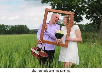 Couple lovers walking in a green field in summer day