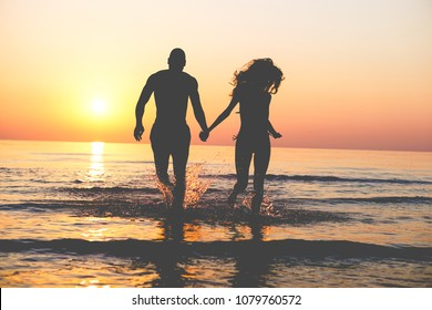 Couple of lovers walking inside water on tropical beach in summer vacation at sunset - Young people enjoying holidays - Love, travel and landscape concept - Focus on silhouettes