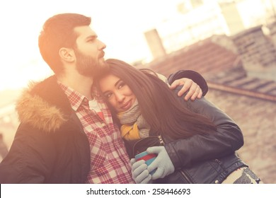 Couple loving each other outdoors on a coffee break.