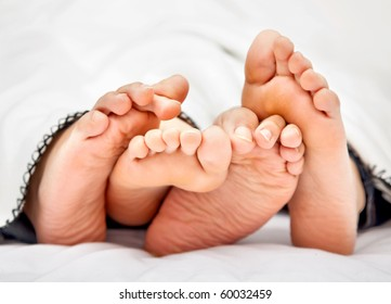 Couple lying barefoot in bed under the blankets