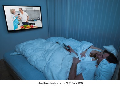Couple Lying In Bed With Blanket Watching Television