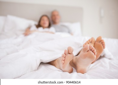 Couple lying in a bed with the camera focus on their feet