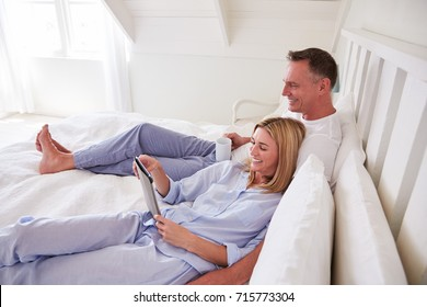 Couple Lying In Bed Looking At Digital Tablet Together