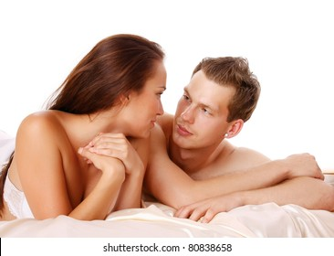 A couple is lying in bed and looking to each other