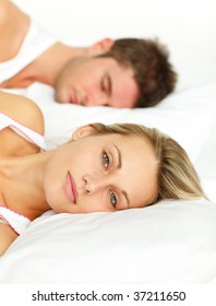 Couple lying in bed. Man sleeping and woman looking at the camera