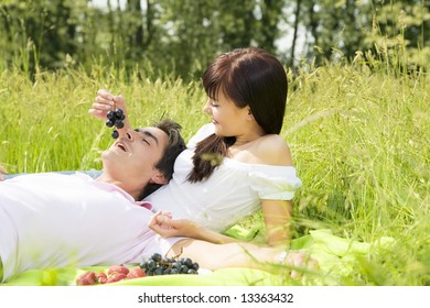 Couple lying in grass, smiling and eating grapes
