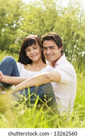 Couple lying in grass, smiling and hugging