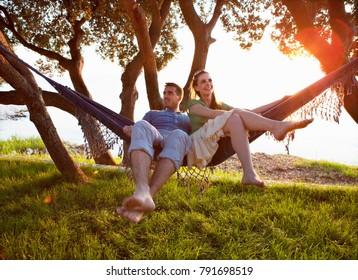 Couple lying in hammock at beach