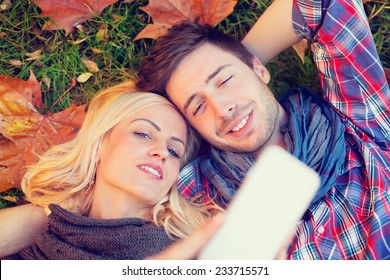 couple lying on autumn leaves make a Selfie