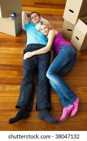 Couple lying on the floor with boxes around. Moving house