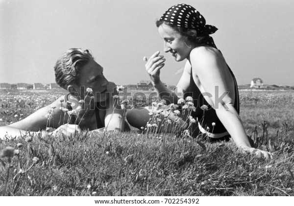 Couple lying on the grass in field