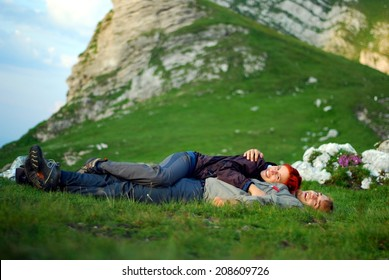 a couple lying on grass in mountains
